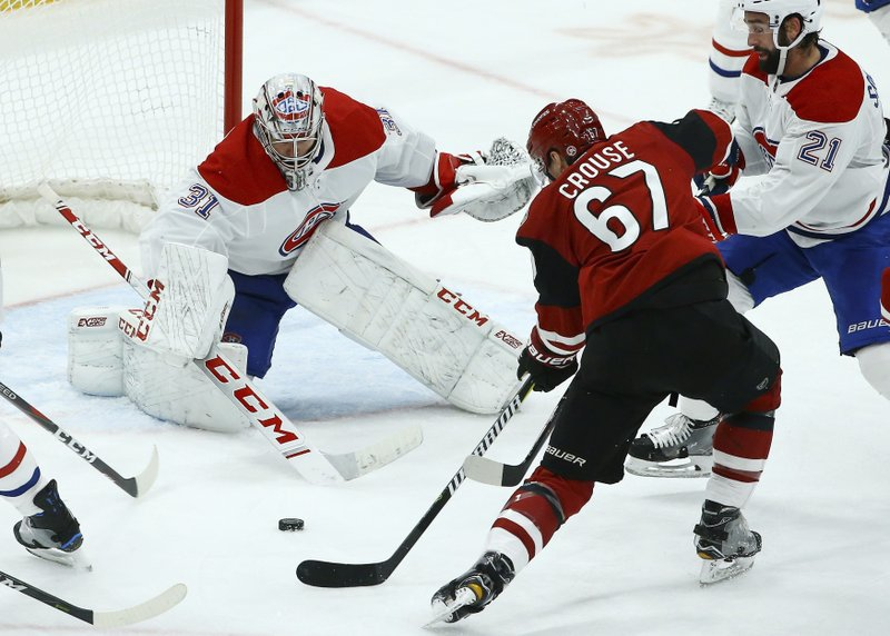 Montreal Canadiens goaltender Carey Price (31) gets into position to make a save on a shot by Arizona Coyotes left wing Lawson Crouse (67) as Canadiens defenseman David Schlemko (21) applies pressure during the second period of an NHL hockey game Thursday, Dec. (AP Photo/Ross D. Franklin)