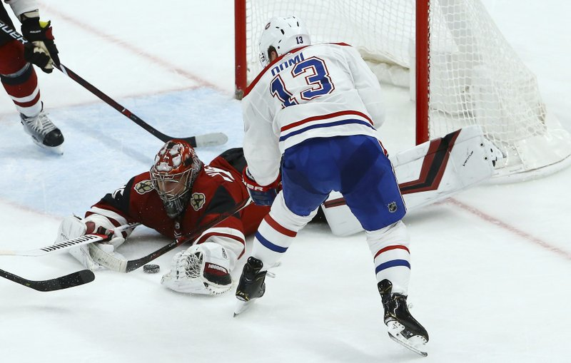 Montreal Canadiens left wing Max Domi (13) gets his shot blocked by Arizona Coyotes goaltender Darcy Kuemper, left, during the second period of an NHL hockey game Thursday, Dec. (AP Photo/Ross D. Franklin)