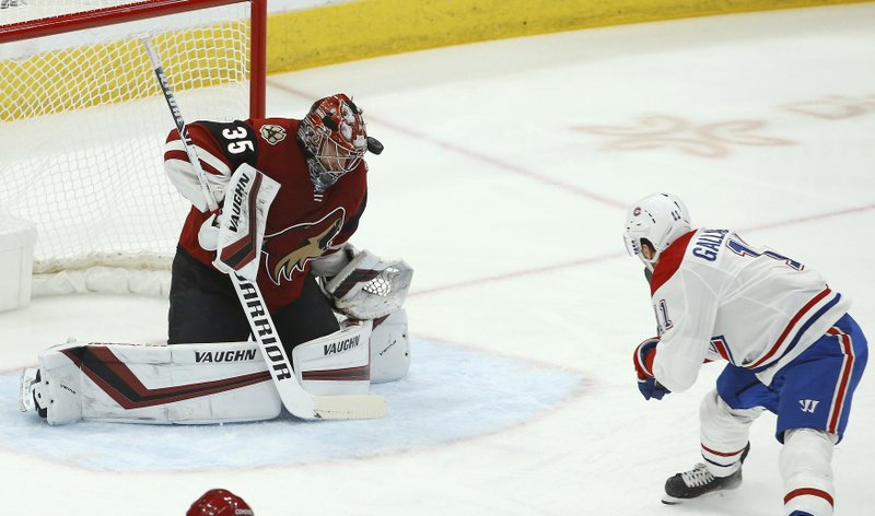 Montreal Canadiens right wing Brendan Gallagher (11) shoots the puck off the head of Arizona Coyotes goaltender Darcy Kuemper (35) during the first period of an NHL hockey game Thursday, Dec. (AP Photo/Ross D. Franklin)