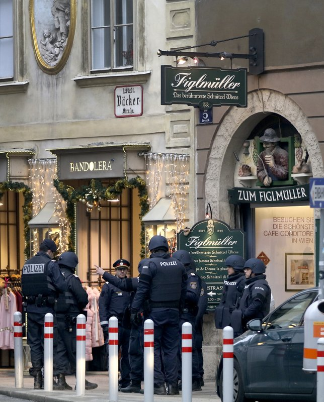 Police officers investigate a crime scene in Vienna, Austria, Friday, Dec. 21, 2018. A shooting Friday in central Vienna has killed one person and wounded another, Austrian authorities said. (AP Photo/Ronald Zak)