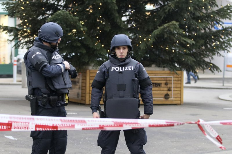 Police officers stand guard close to a crime scene in Vienna, Austria, Friday, Dec. 21, 2018. A shooting Friday in central Vienna has killed one person and wounded another, Austrian authorities said. (AP Photo/Ronald Zak)