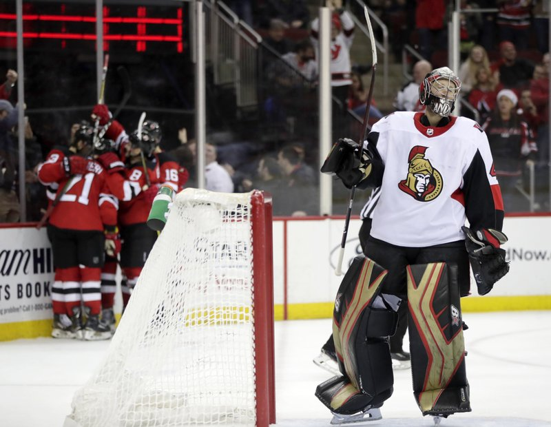 Ottawa Senators goaltender Craig Anderson, right, reacts after giving up a goal to New Jersey Devils center Nico Hischier, of Switzerland, as the Devils celebrate at left during the second period of an NHL hockey game, Friday, Dec. (AP Photo/Julio Cortez)
