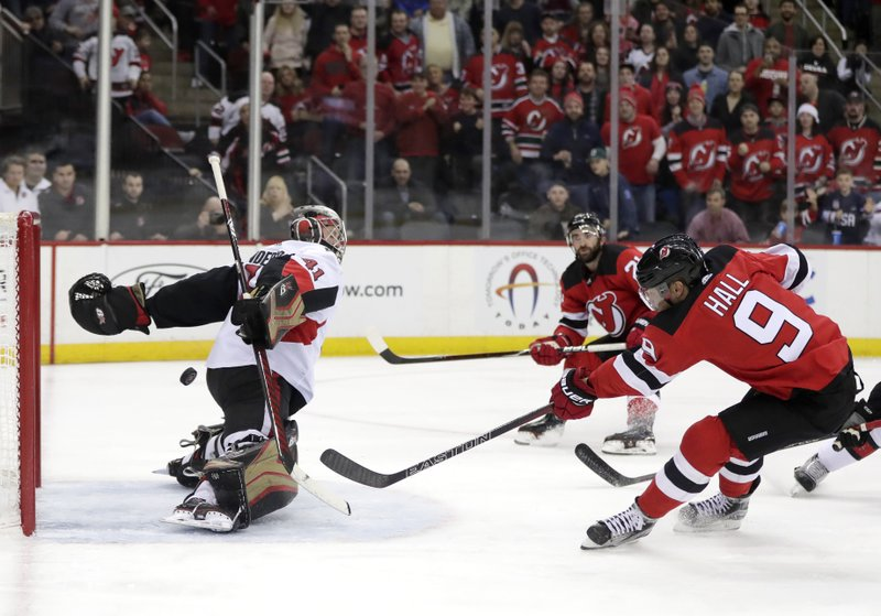 New Jersey Devils left wing Taylor Hall (9) scores a goal on Ottawa Senators goaltender Craig Anderson (41) during the second period of an NHL hockey game Friday, Dec. (AP Photo/Julio Cortez)