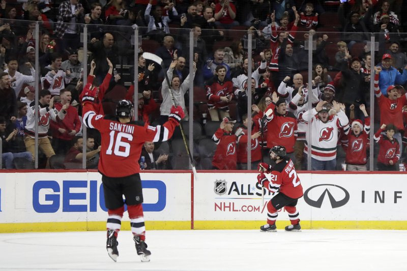 New Jersey Devils right wing Kyle Palmieri, right, and defenseman Steven Santini (16) celebrate Palmieri's first-period goal against the Ottawa Senators during an NHL hockey game Friday, Dec. (AP Photo/Julio Cortez)