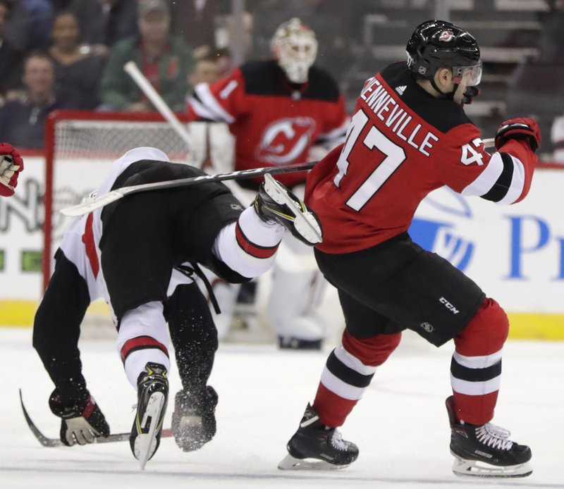 Ottawa Senators defenseman Thomas Chabot, left, loses his balance while competing for the puck with New Jersey Devils center John Quenneville (47) during the second period of an NHL hockey game Friday, Dec. (AP Photo/Julio Cortez)