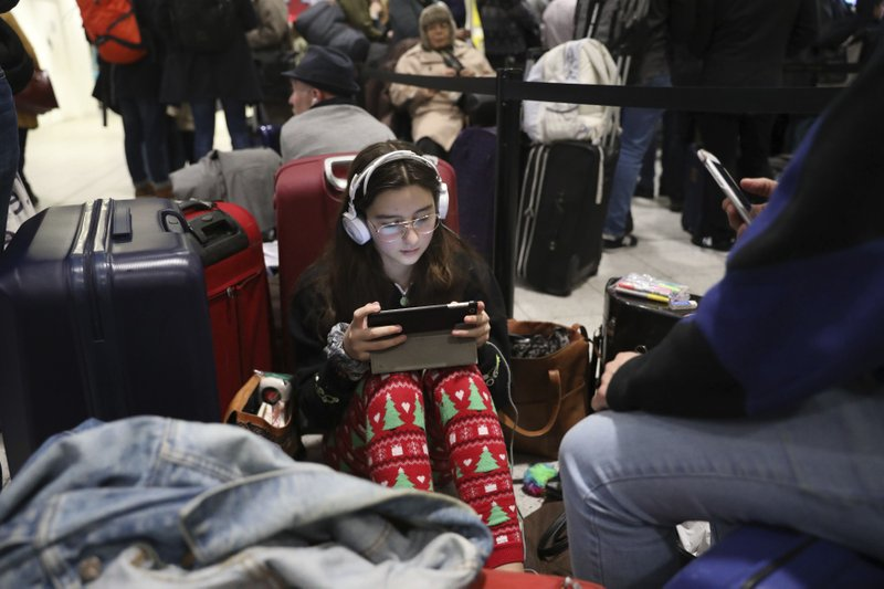 Passengers at Gatwick airport settle down to wait for their flights following the delays and cancellations brought on by drone sightings near the airfield, in London, Friday Dec. (John Stillwell/PA via AP)