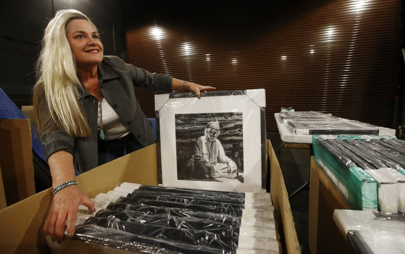 Alison Goldwater Ross, the granddaughter of former Arizona Sen. Barry Goldwater who is trying to save and digitize her grandfather's photographic archive, smiles as she unpacks some of her grandfather's framed photographic work at Scottsdale's Museum of the West Thursday, Dec. (AP Photo/Ross D. Franklin)