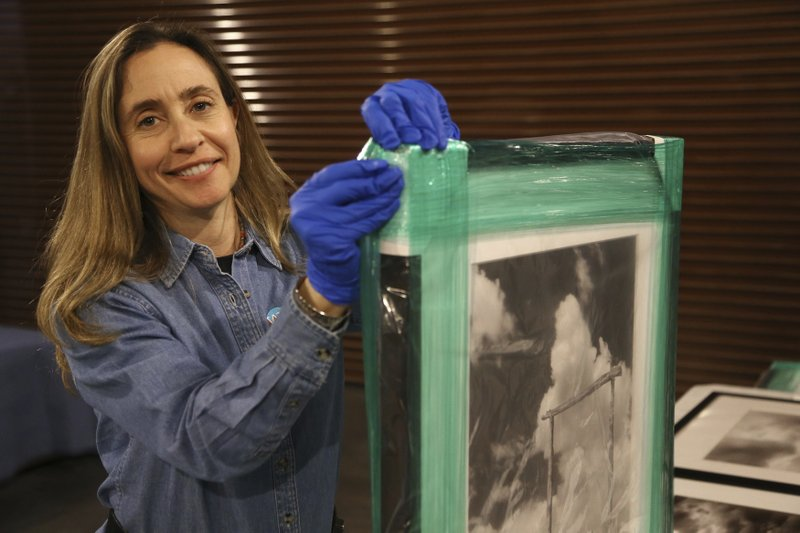 Tricia Loscher, assistant director and chief curator at Scottsdale's Museum of the West, smiles as she carefully unpacks a framed photograph taken by former Arizona Sen. (AP Photo/Ross D. Franklin)