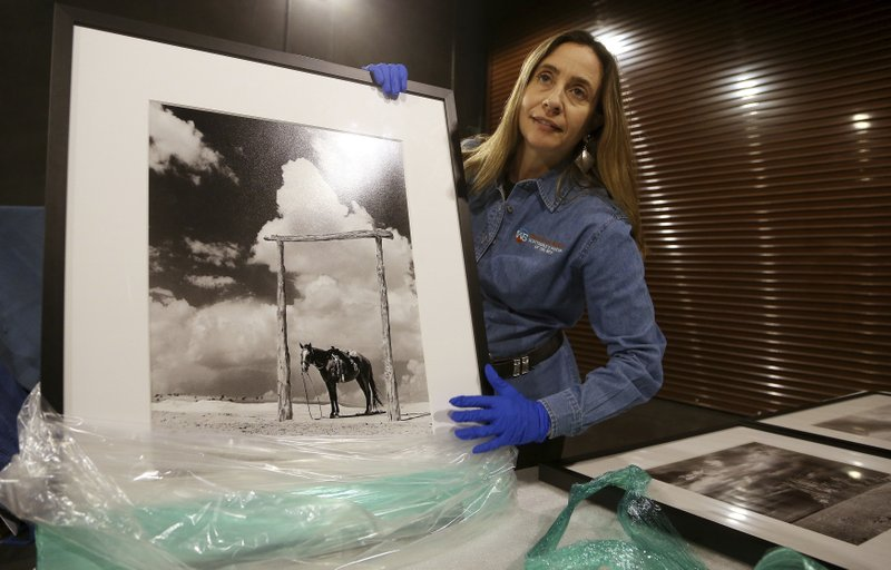 Tricia Loscher, assistant director and chief curator at Scottsdale's Museum of the West, carefully unpacks a framed photograph taken by former Arizona Sen. (AP Photo/Ross D. Franklin)