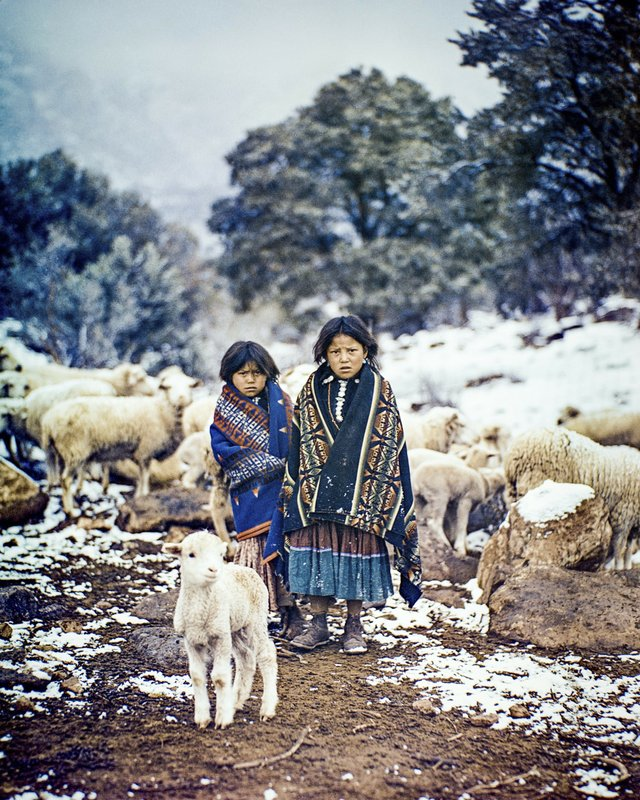 This photo provided by Barry & Peggy Goldwater Foundation,  two young Navajo girls, Lillie and Ethel One Salt, tend their sheep in the snow in this photograph entitled