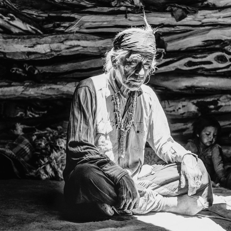 This photograph taken by Barry Goldwater in 1948 on the north side of Navajo Mountain in Arizona shows an elderly man sitting cross-legged and illuminated by a shaft of light. (AP Photo/Barry Goldwater/Courtesy of the Barry & Peggy Goldwater Foundation)