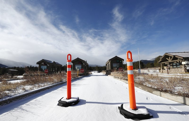 A lane is blocked to an unattended toll booth at Rocky Mountain National Park Saturday, Dec. 22, 2018, in Estes Park, Colo. (AP Photo/David Zalubowski)