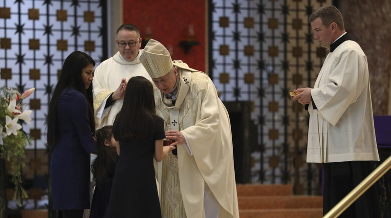 Officer Eduardo Marmolejo's family offers the gifts to Cardinal Blase Cupich as he leads the funeral mass for fallen Chicago police Officer Eduardo Marmolejo at St. (Abel Uribe/Chicago Tribune via AP, Pool)