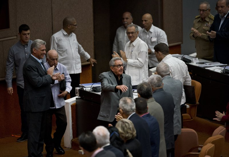 Cuba's President Miguel Diaz-Canel, left, applauds as former President Raul Castro, center, greets members of the Assembly before the start of a session to debate the draft of a new Constitution, at the Convention Palace in Havana, Cuba, Friday, Dec. (AP Photo/Ramon Espinosa)