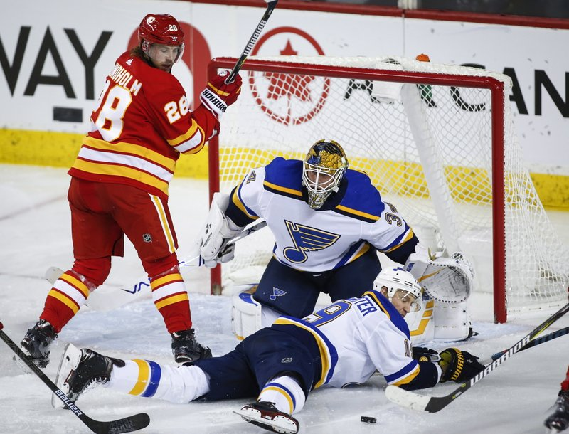 St. Louis Blues' Jay Bouwmeester, right, dives in front of the puck as goalie Jake Allen, center, and Calgary Flames' Elias Lindholm, of Sweden, watch during the second period of an NHL hockey game Saturday, Dec. (Jeff McIntosh/The Canadian Press via AP)
