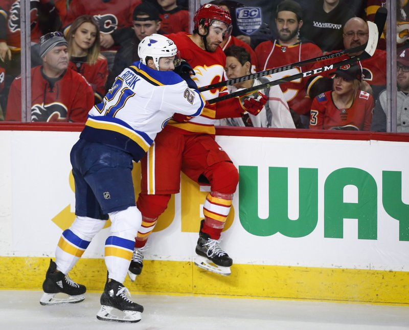 St. Louis Blues' Tyler Bozak, left, checks Calgary Flames' T.J. Brodie during the second period of an NHL hockey game Saturday, Dec. (Jeff McIntosh/The Canadian Press via AP)
