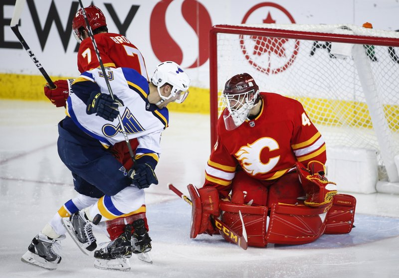 St. Louis Blues' David Perron, center, is hit in the shin by a slap shot as Calgary Flames goalie Mike Smith watches during the third period of an NHL hockey game Saturday, Dec. (Jeff McIntosh/The Canadian Press via AP)