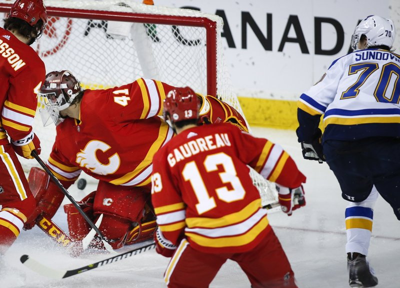 St. Louis Blues' Oskar Sundqvist, right, of Sweden, scores against Calgary Flames goalie Mike Smith during third-period NHL hockey game action in Calgary, Alberta, Saturday, Dec. (Jeff McIntosh/The Canadian Press via AP)