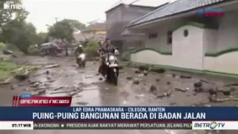 In this image made from video,  people on motorbikes move past debris on street after a tsunami hit the coast in Serang city, in Banten Province, Indonesia, Sunday, Dec. (METRO TV via AP)