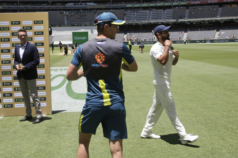 Australian captain Tim Paine, center, and his India counterpart Virat Kohli walk past each other without acknowledgement during the post match interviews following the second cricket test between Australia and India in Perth, Australia, Tuesday, Dec. (AP Photo/Trevor Collens)