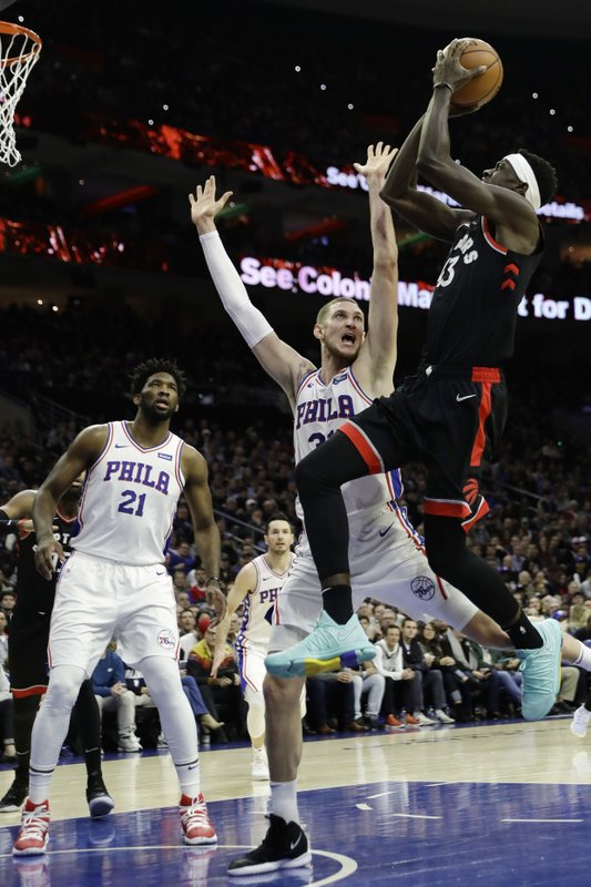 Toronto Raptors' Pascal Siakam, right, goes up for a shot against Philadelphia 76ers' Mike Muscala during the first half of an NBA basketball game, Saturday, Dec. (AP Photo/Matt Slocum)