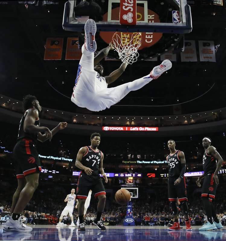 Philadelphia 76ers' Joel Embiid, top, hangs on the rim after a dunk during the first half of an NBA basketball game against the Toronto Raptors, Saturday, Dec. (AP Photo/Matt Slocum)