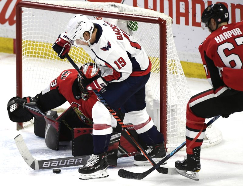 Ottawa Senators goaltender Mike McKenna (33) uses his stick to control the puck in the crease as defenseman Ben Harpur (67) tries to force back the stick of Washington Capitals center Nicklas Backstrom (19) during the third period of an NHL hockey game, Saturday, Dec. (Justin Tang/The Canadian Press via AP)