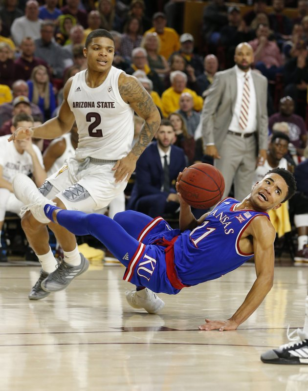 Kansas guard Devon Dotson (11) loses the ball in front of Arizona State guard Rob Edwards during the first half of an NCAA college basketball game Saturday, Dec. (AP Photo/Rick Scuteri)