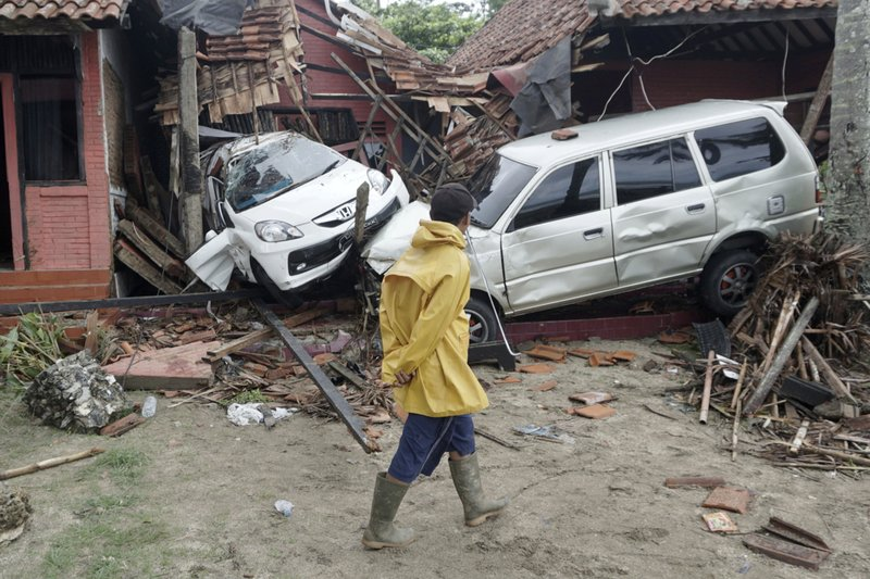 A villager walks past a car damaged by a tsunami, in Carita, Indonesia, Sunday, Dec. 23, 2018. The tsunami apparently caused by the eruption of an island volcano killed a number of people around Indonesia's Sunda Strait, sending a wall of water crashing some 65 feet (20 meters) inland and sweeping away hundreds of houses including hotels, the government and witnesses said. (AP Photo/Dian Triyuli Handoko)