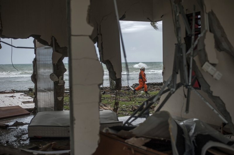 A rescuer is seen through a damaged house as he takes part in a search operation of tsunami victims in Carita, Indonesia, Sunday, Dec. (AP Photo/Fauzy Chaniago)