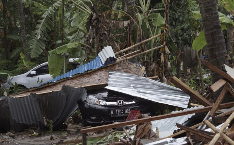 Cars are covered by debris at an area ravaged by a tsunami, in Carita, Indonesia, Sunday, Dec. 23, 2018. (20 meters) inland and sweeping away hundreds of houses including hotels, the government and witnesses said. (AP Photo/Dian Triyuli Handoko)