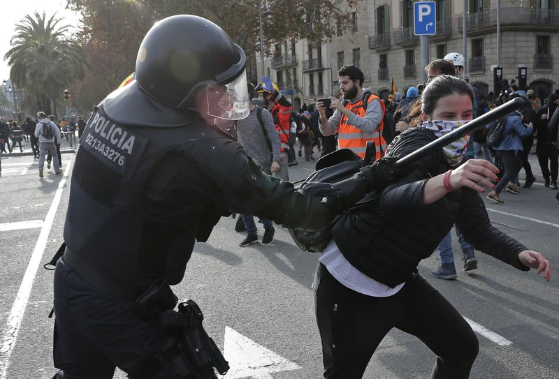 A police officer beats a demonstrator during a protest against Spain's cabinet holding a meeting in Barcelona Spain, Friday Dec. (AP Photo/Manu Fernandez)