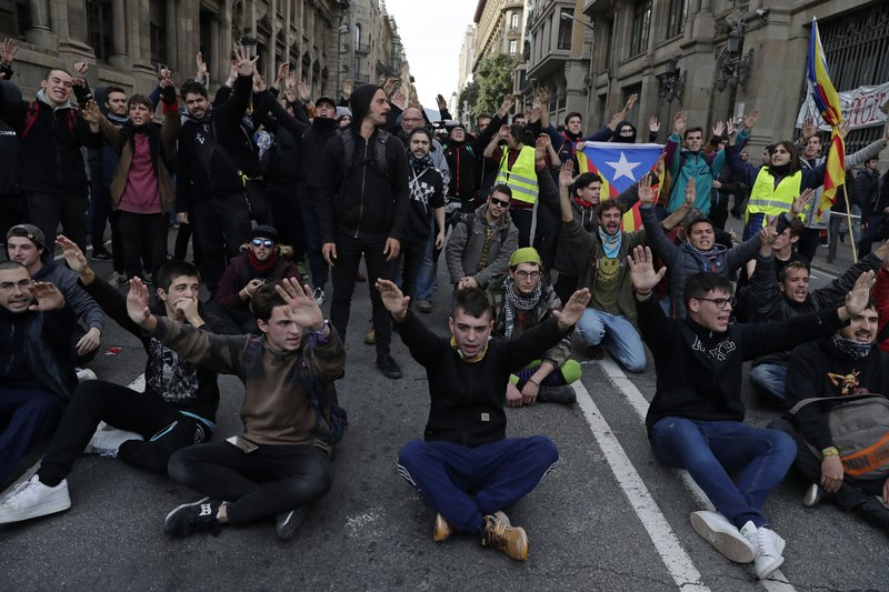 Pro-independence demonstrators sit down on the street during a protest against Spain's cabinet holding a meeting in Barcelona Spain, Friday Dec. (AP Photo/Manu Fernandez)