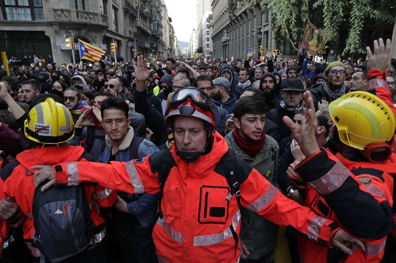 Firefighters help to control the demonstrators during a protest against Spain's cabinet holding a meeting in Barcelona Spain, Friday Dec. (AP Photo/Manu Fernandez)