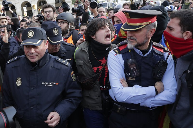 Pro-independence demonstrators shout at a mossos d'esquadra Cataonia regional police officer accompanied by Spanish national officers during a protest against Spain's cabinet holding a meeting in Barcelona Spain, Friday Dec. (AP Photo/Manu Fernandez)