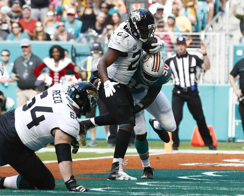 Jacksonville Jaguars running back Leonard Fournette (27) scores a touchdown as Miami Dolphins defensive end Charles Harris (90) attempts to tackle, during the first half of an NFL football game, Sunday, Dec. (64) is at left, (AP Photo/Brynn Anderson)