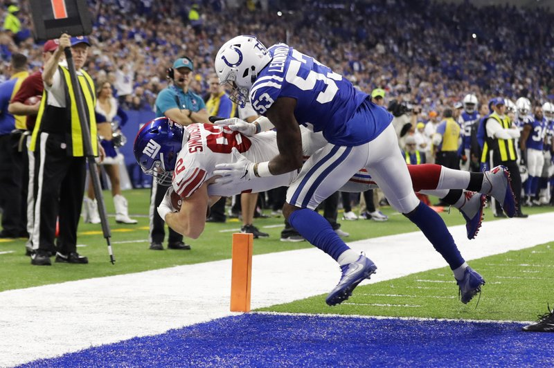New York Giants tight end Scott Simonson (82) dives in for a touchdown under Indianapolis Colts outside linebacker Darius Leonard (53) during the first half of an NFL football game in Indianapolis, Sunday, Dec. (AP Photo/Darron Cummings)
