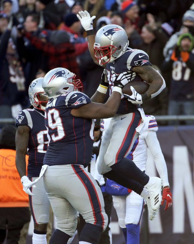 New England Patriots running back James White, right, celebrates his touchdown run with lineman Shaq Mason during the first half of an NFL football game against the Buffalo Bills, Sunday, Dec. (AP Photo/Elise Amendola)