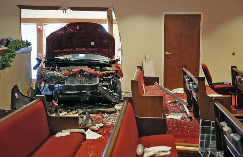 A car that crashed into the entrance of the Crossroads United Methodist Church located at 1100 Hague Avenue is visible from inside of the church on the morning of Sunday, December 23, 2018 in Columbus, Ohio. (Brooke LaValley/The Columbus Dispatch via AP)