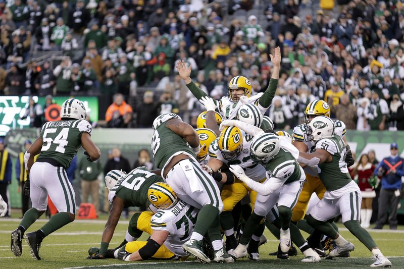 Green Bay Packers quarterback Aaron Rodgers, top, gestures after scoring a touchdown against the New York Jets during the second half of an NFL football game, Sunday, Dec. (AP Photo/Seth Wenig)