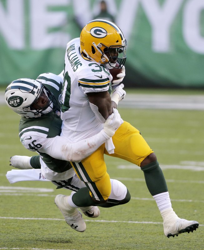 Green Bay Packers running back Jamaal Williams, right, is tackled by New York Jets linebacker Neville Hewitt during the second half of an NFL football game, Sunday, Dec. (AP Photo/Seth Wenig)