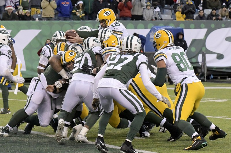 Green Bay Packers quarterback Aaron Rodgers, top, reaches over a host of players for a touchdown against the New York Jets during the second half of an NFL football game, Sunday, Dec. (AP Photo/Bill Kostroun)