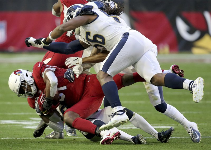 Arizona Cardinals running back David Johnson (31) is hit by Los Angeles Rams linebacker Dante Fowler (56) during the second half of an NFL football game, Sunday, Dec. (AP Photo/Ross D. Franklin)