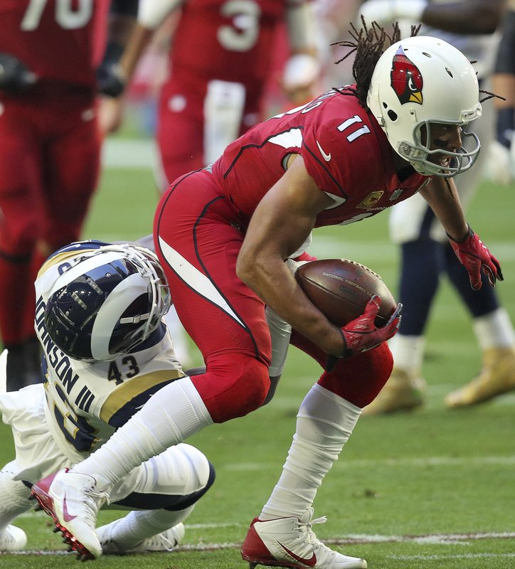 Arizona Cardinals wide receiver Larry Fitzgerald (11) is hit by Los Angeles Rams strong safety John Johnson (43) during the first half of an NFL football game, Sunday, Dec. (AP Photo/Ross D. Franklin)