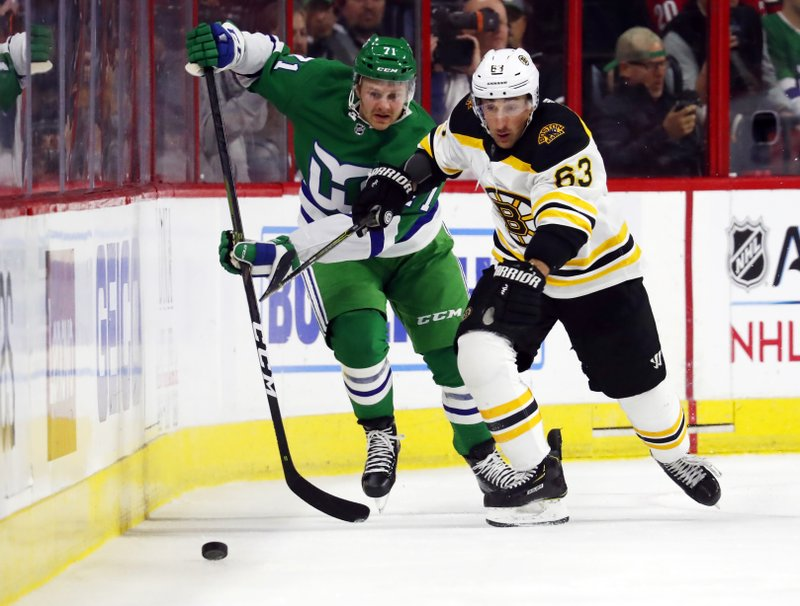 Boston Bruins' Brad Marchand (63) eyes the puck after battling Carolina Hurricanes' Lucas Wallmark (71) for position during the first period of an NHL hockey game, Sunday, Dec. (AP Photo/Karl B DeBlaker)