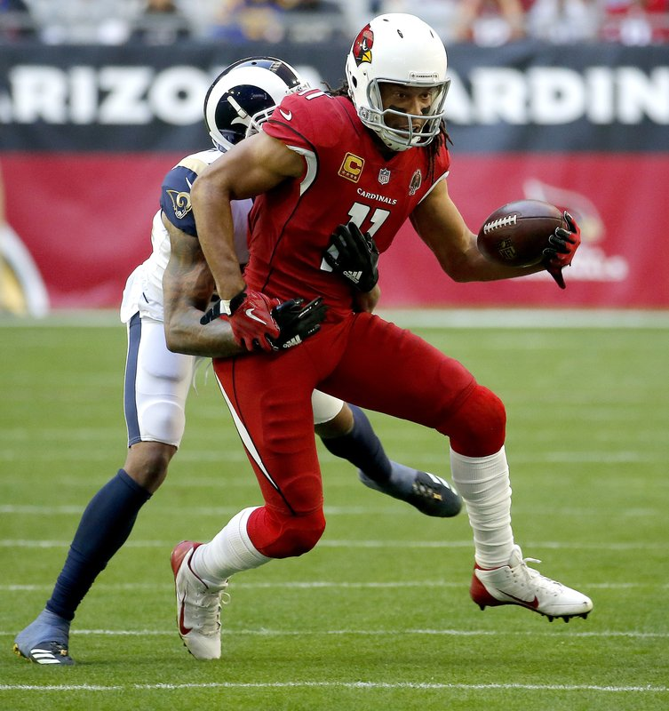 Arizona Cardinals wide receiver Larry Fitzgerald (11) is tries to elude Los Angeles Rams cornerback Marcus Peters (22) during the first half of an NFL football game, Sunday, Dec. (AP Photo/Rick Scuteri)