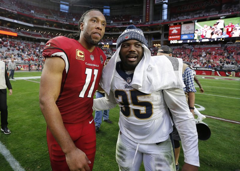 Arizona Cardinals wide receiver Larry Fitzgerald greets Los Angeles Rams running back C.J. Anderson after an NFL football game, Sunday, Dec. (AP Photo/Rick Scuteri)