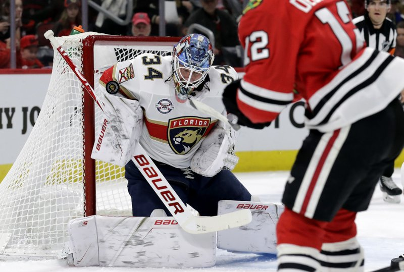 Florida Panthers goalie James Reimer (34) blocks a shot by Chicago Blackhawks left wing Alex DeBrincat (12) during the first period of an NHL hockey game Sunday, Dec. (AP Photo/Nam Y. Huh)