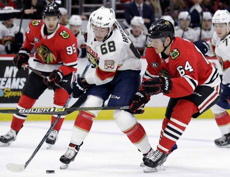 Florida Panthers left wing Mike Hoffman (68) controls the puck against Chicago Blackhawks center David Kampf (64) during the second period of an NHL hockey game Sunday, Dec. (AP Photo/Nam Y. Huh)