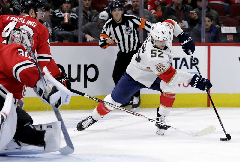 Florida Panthers defenseman MacKenzie Weegar, right, controls the puck against Chicago Blackhawks defenseman Gustav Forsling and goalie Cam Ward during the second period of an NHL hockey game Sunday, Dec. (AP Photo/Nam Y. Huh)